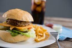 Закройте вверх фраев гамбургера, который и француза служат в плите Стоковые Изображения RF