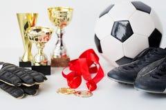 Закройте вверх футбола, ботинок, перчаток, чашки и медали Стоковые Изображения RF