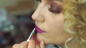 Закройте вверх художника состава крася красный состав губ к красивой маленькой девочке в студии Красное lipctick видеоматериал