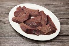 Закройте вверх частей свежей сырцовой печени говядины, плиты фарфора на деревянной предпосылке Стоковое фото RF
