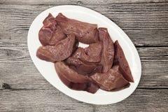 Закройте вверх частей свежей сырцовой печени говядины, плиты фарфора на деревянной предпосылке Стоковые Фото
