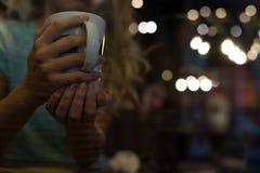 Закройте вверх чашки Женщина наслаждается в кофе стоковое изображение rf