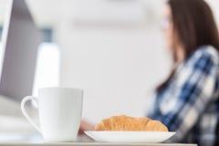 Закройте вверх чашки кофе или чая и свежего круассана шоколада рядом с молодой женской деятельностью на ее настольном компьютере стоковая фотография