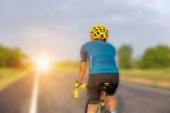 Закройте вверх человека велосипедиста с путем клиппирования над запачканным утром стоковое изображение