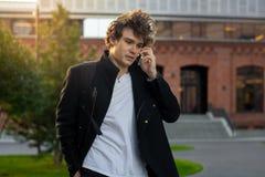 Закройте вверх человека в черном пальто говоря мобильным телефоном на предпосылке городского пейзажа стоковые фото