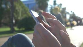 Закройте вверх человека используя мобильный умный телефон, на открытом воздухе Закройте вверх мужские руки отправляя SMS на его с акции видеоматериалы