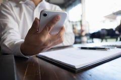 Закройте вверх человека используя мобильный умный телефон на таблице стоковые фото