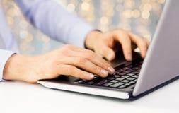 Закройте вверх человека печатая на клавиатуре компьтер-книжки стоковое фото rf