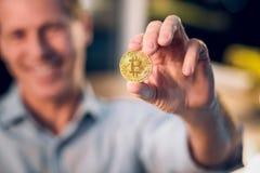 Закройте вверх человека показывая bitcoin стоковое фото