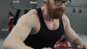 Закройте вверх человека разрабатывая на велотренажере на спортзале Человек делает на велотренажере сток-видео