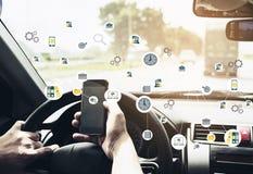 Закройте вверх человека управляя автомобилем опасно пока использующ передвижное pho Стоковое Изображение