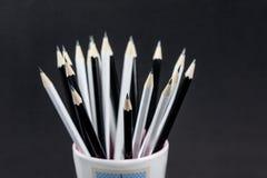 Закройте вверх черно-белого заточенного карандаша в чашке стоковые фото