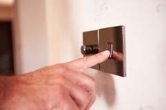 Закройте вверх человека включая электрический выключатель Стоковые Изображения RF