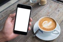 Закройте вверх человека используя умный телефон с пустой чернью и чашку  Стоковые Изображения RF