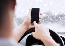 Закройте вверх человека используя smartphone пока управляющ автомобилем Стоковые Изображения RF