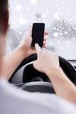 Закройте вверх человека используя smartphone пока управляющ автомобилем Стоковые Фотографии RF