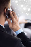 Закройте вверх человека используя smartphone пока управляющ автомобилем Стоковая Фотография