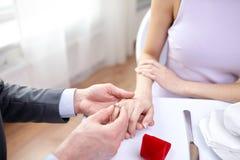 Закройте вверх человека кладя кольцо к его пальцу жениха Стоковые Фотографии RF