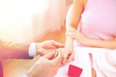 Закройте вверх человека кладя кольцо к его пальцу жениха Стоковые Изображения