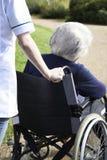 Закройте вверх человека осуществляющего уход нажимая старшую женщину в кресло-коляске Стоковое фото RF