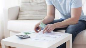 Закройте вверх человека при калькулятор подсчитывая деньги сток-видео