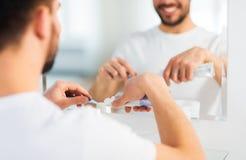 Закройте вверх человека сжимая зубную пасту на зубной щетке Стоковые Изображения RF