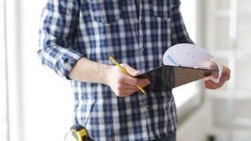 Закройте вверх человека смотря и писать к доске сзажимом для бумаги