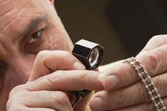 Закройте вверх человека смотря ювелирные изделия через лупу Стоковая Фотография