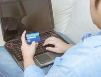 Закройте вверх человека с портативным компьютером и кредитной карточкой дома Стоковое фото RF