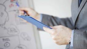 Закройте вверх человека с схемой и доской сзажимом для бумаги дела акции видеоматериалы