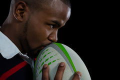 Закройте вверх шарика рэгби мужского игрока целуя Стоковые Фото