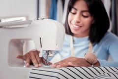 Закройте вверх швейной машины будучи использованным умелым портноем стоковые фото