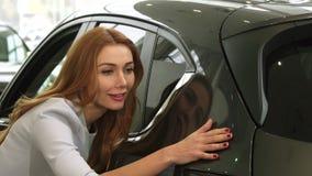 Закройте вверх шикарной женщины рассматривая новый автомобиль на дилерских полномочиях сток-видео