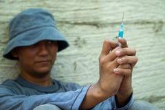 Закройте вверх шприца и иглы в руке человека наркомана лекарства бродяга используя иглу впрыскивая жидкость Концепция лекарства и стоковое изображение rf