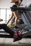 Закройте вверх людей используя оборудование в занятом спортзале Стоковая Фотография