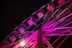 Закройте вверх яркого розового колеса ferris осветил вверх против темного неба во время фестиваля в городе стоковая фотография