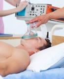 Закройте вверх anesthetist кладя кислородный изолирующий противогаз дальше Стоковое Изображение RF