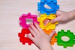 Закройте вверх child& x27; s вручает играть с красочным пластичным конструктором на деревянной предпосылке Стоковое Изображение RF