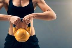 Закройте вверх kettlebell спортсменки поднимаясь с 2 руками стоковая фотография
