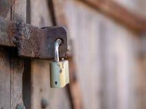 Закройте вверх padlock обеспечивая ржавую и выдержанную деревянную дверь стоковое изображение