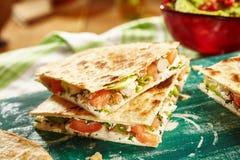 Закройте вверх quesadillas цыпленка на разделочной доске Стоковая Фотография