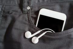 Закройте вверх smartphone и наушника в переднем карманн на брюках Стоковое Фото