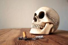 Закройте вверх stub сигареты и blured человеческого черепа Стоковое Изображение