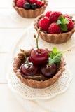 Закройте вверх tartlets шоколада с сливк шоколада, свежими клубниками, полениками, голубиками, красными смородинами и вишнями стоковые изображения