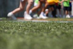 Закройте до теннисной обуви, детей бежать на траве стоковое изображение rf