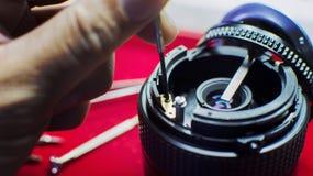 Закрутка отвертки ремонтируя в тело объектива фотоаппарата селективно Стоковые Фото