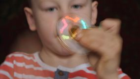 Закручивая игрушка, обтекатель втулки, в руках белокурого мальчика видеоматериал