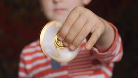 Закручивая игрушка, обтекатель втулки, в руках белокурого мальчика акции видеоматериалы