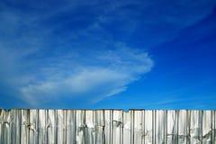Закрывает загородку цинка как стена текстуры предпосылки с красивым голубым небом стоковая фотография rf