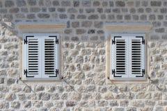 2 закрывали окна в каменной стене дома Стоковое Изображение
